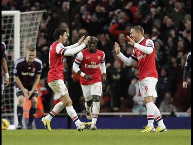 Podolski goal secures Arsenal victory over Stoke